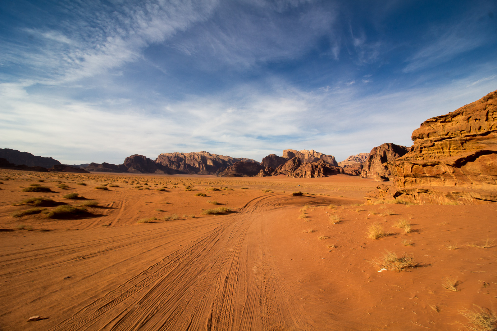 A wide view of the Mars-like terrain of Wadi Rum. So Mars-like that it's where they shot The Martian. Tire tracks follow behind.