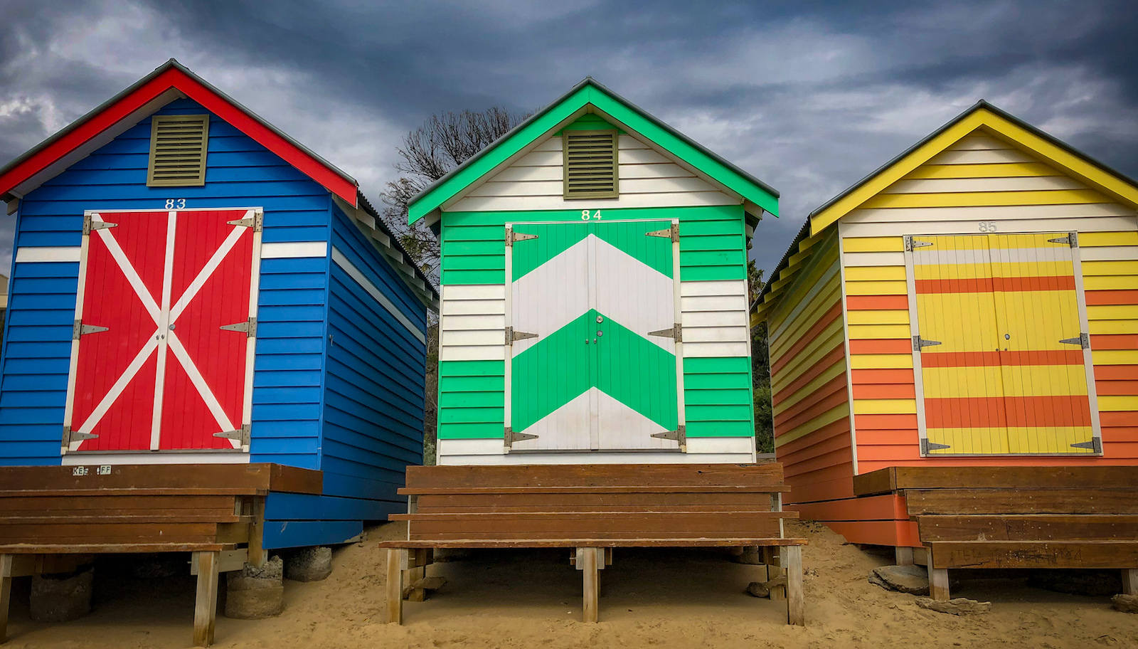 Three brightly colored huts rise from the sandy shore. What does one do in a bathing house?