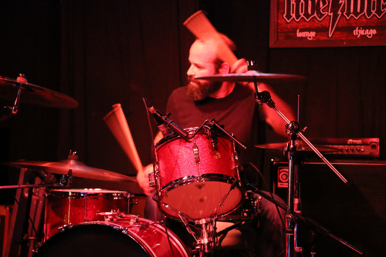 An incredibly good looking bearded man plays drums